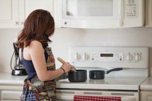 kobieta gotuje obiad w garnkach